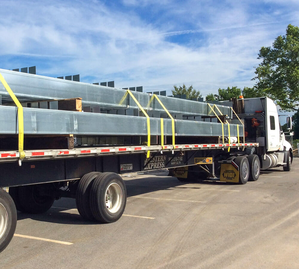 pre-engineered steel frame columns for carports are delivered for installation